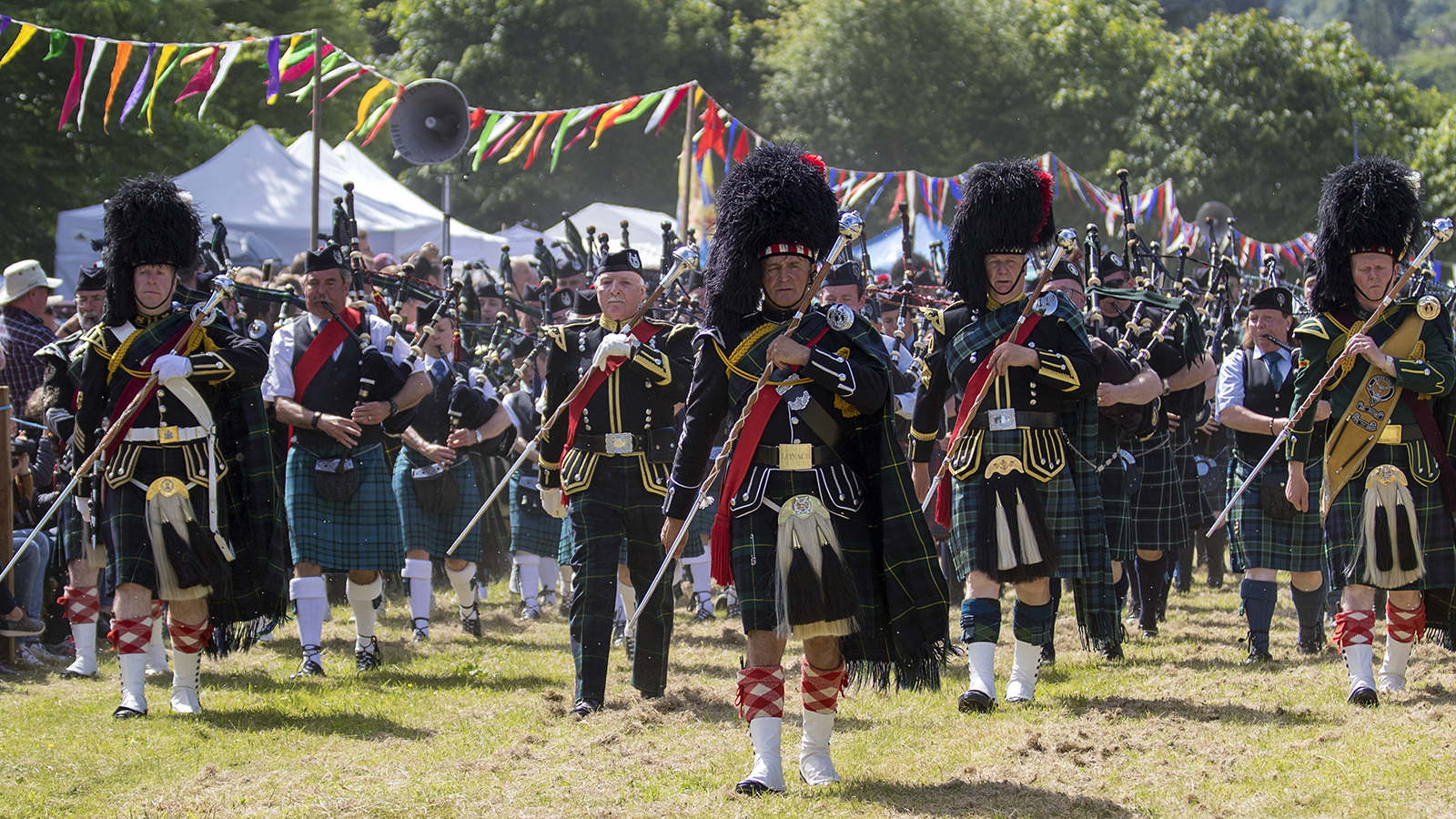 Massed pipe bands at a Highland Games event in Scotland.