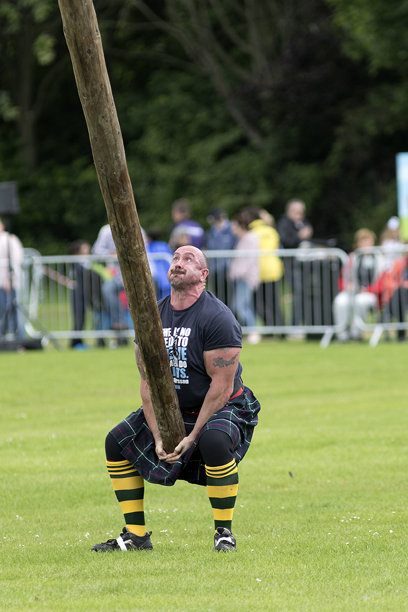A competitor in the caber toss at a Highland Games event in Scotland