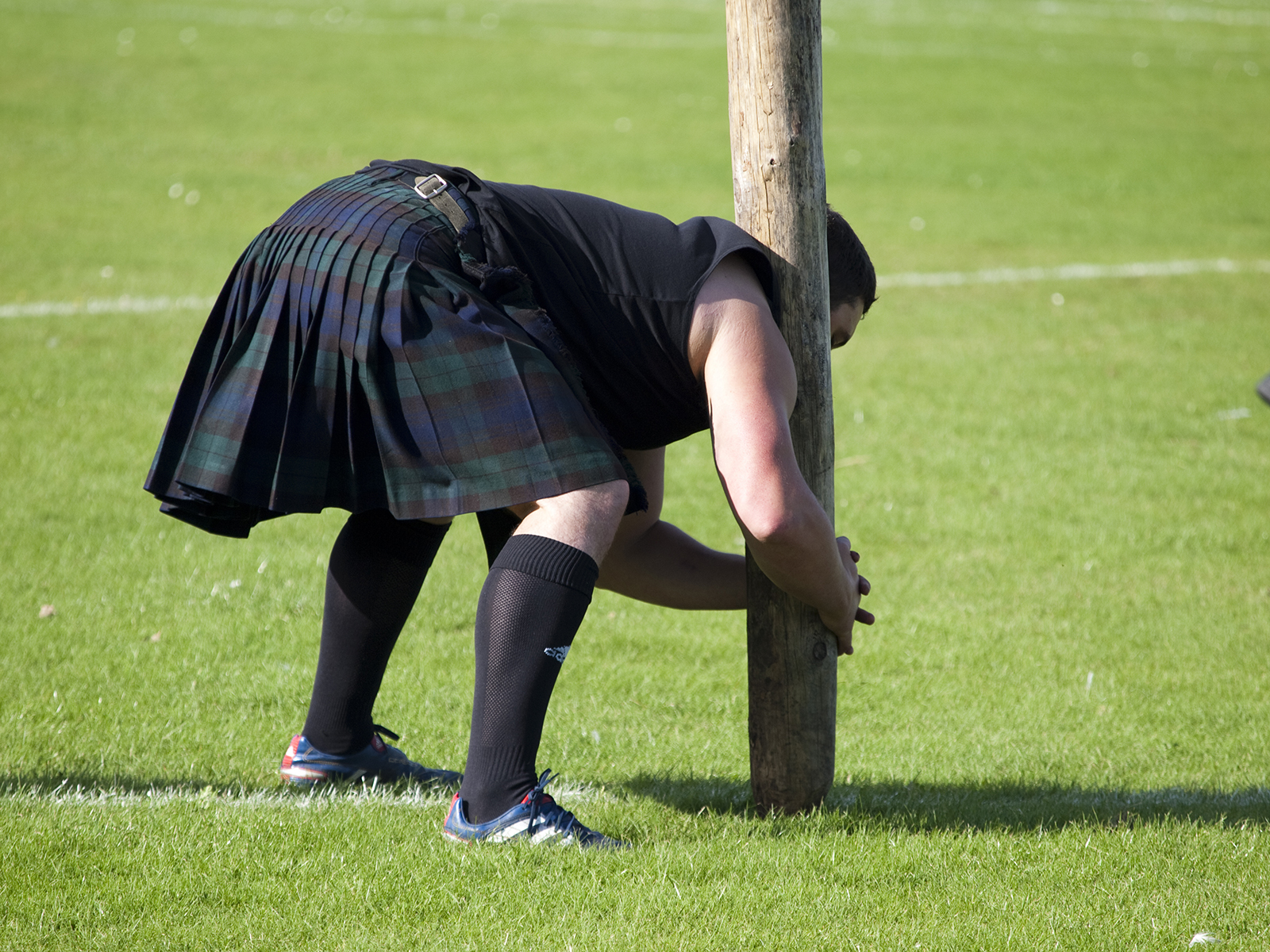 A competitor lifting the caber at a Highland Games event in Scotland